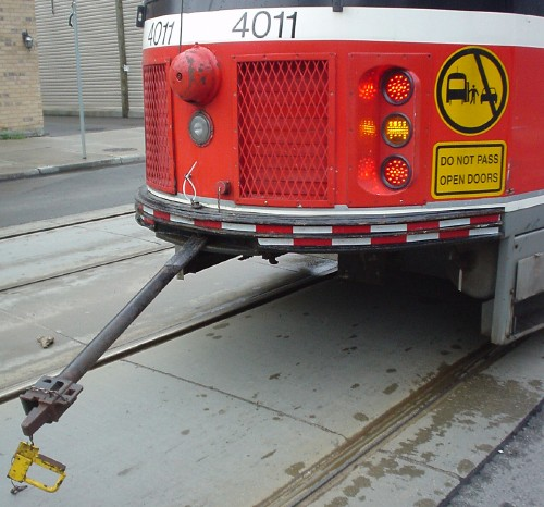 Metal rod with dangling yellow connector projects from rear of red streetcar