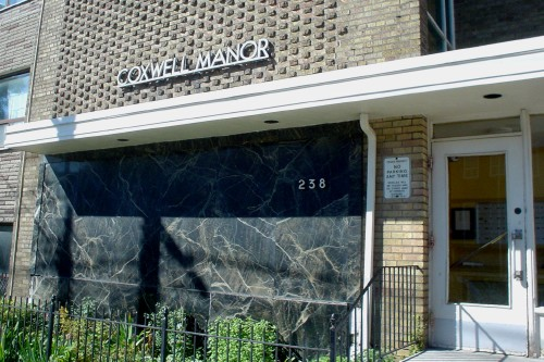Building with stone front panel and raised-brick façade has a sign reading COXWELL MANOR in Futura