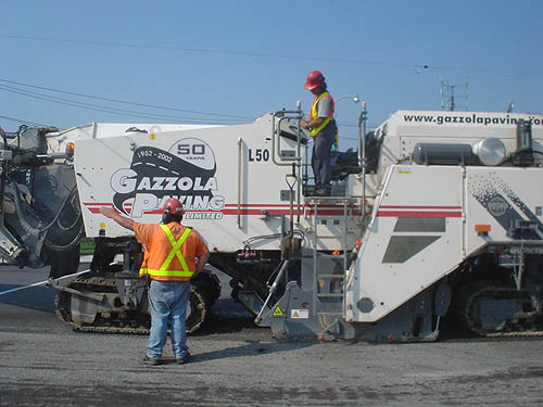 Man in safety vest and hard hat points as giant Gazzola Paving grader lumbers by on treads