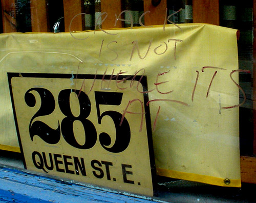Sign in window reads '285 Queen St. E.'; on the glass, graffiti reads 'Crack is not where it's at'