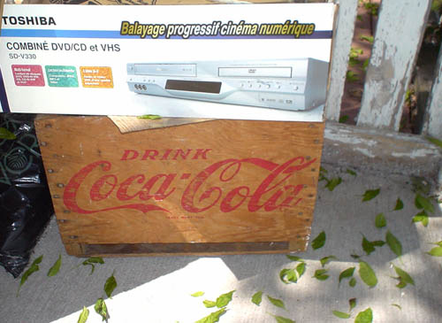 Packaging for Toshiba DVD/VHS player-recorder typeset in Arial sits atop vintage wooden box emblazoned DRINK Coca-Cola