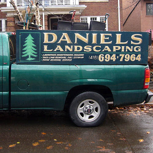 Green pickup truck on rainy, leaf-covered street has wooden walls running up from the bed labelled DANIELS LANDSCAPING in hand-painted type