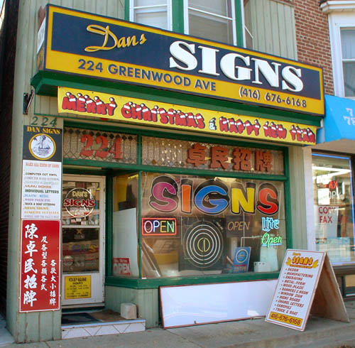 Storefront for Dans Signs shows a riot of coloured fonts and neon signage, with 'MERRY CHRISTMAS & HAPPY NEW YEAR' in a font made of letters with Santa hats