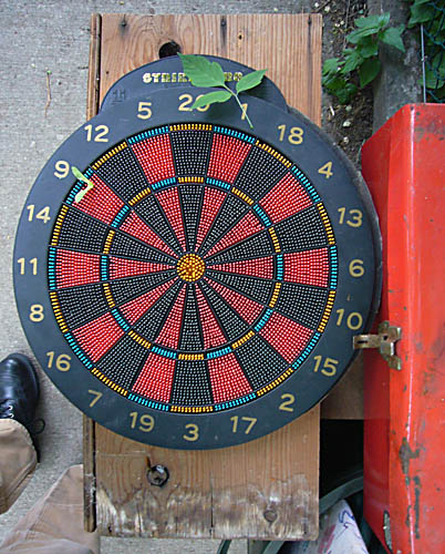 Dartboard, with mechanical or engineering-style numbers around the outside, sits on plank by orange toolbox