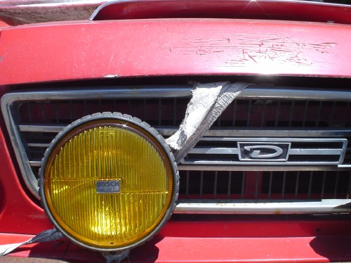 A yellow fog lamp sits offset from the centre of a red Datsun's grille