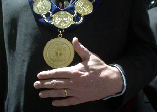 Left hand of a man in a dark suit sits extended beneath a chain of bronze medallions