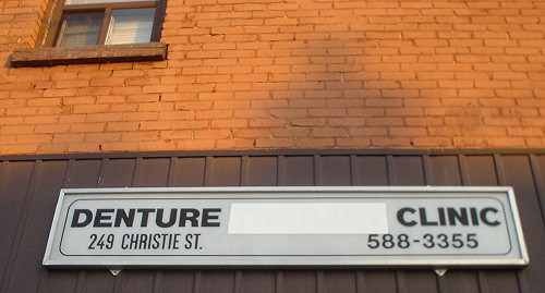 Sign on building reads DENTURE [blanked-out space] CLINIC 249 CHRISTIE ST. 588-3355 in numerous grotesk fonts