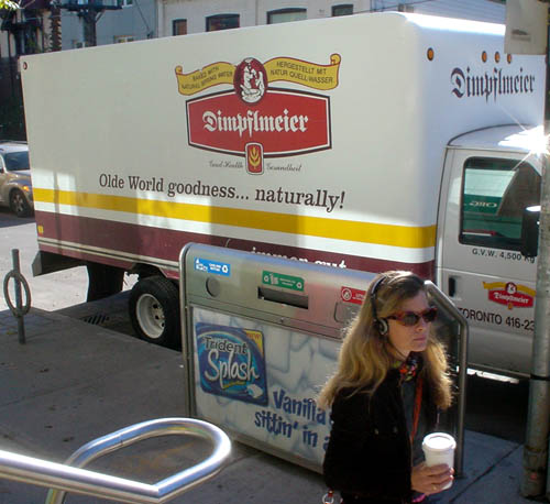 Woman walks past delivery truck labeled Dimpflmeier in blackletter type