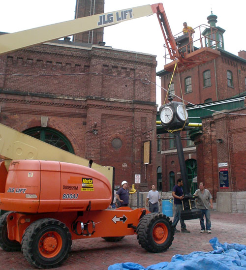Men steady a tall black four-sided clock as a crane lowers it into position on a cobblestone street