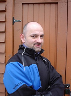Me in black jacket with blue patch, photographed against brown door