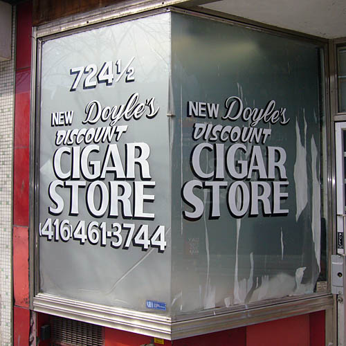 Script and handlettered type on silvery store-window vestibule reads 724½ NEW Doyle's DISCOUNT CIGAR STORE