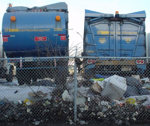 Two blue Toronto garbage trucks – one with a round end, the other squared-off with V-shaped roof – loom behind a wire fence