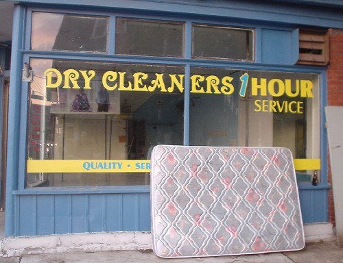 Mattress sits propped against plate-glass window labelled DRY CLEANERS 1 HOUR SERVICE in different fonts