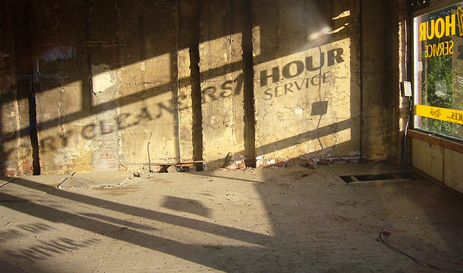 Sign on side window of empty building casts a shadow on another wall: DRY CLEANERS 1 HOUR SERVICE