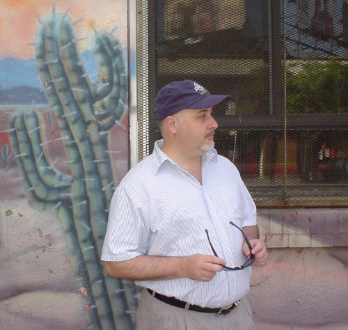 Man in white shirt and blue ballcap holds his shades and looks to the side outside a building's screened window and wall decorated with an airbrushed cactus
