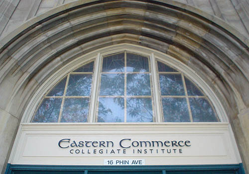 Archway sits over window panes and a door transom labelled Eastern Commerce in uncial, COLLEGIATE INSTITUTE in Frutiger, and 16 PHIN AVE in Helvetica