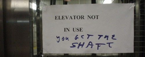 Laser-printed sign tacked onto elevator window reads 'Elevator not in use.' Hand-scrawled graffiti reads 'You get the shaft'