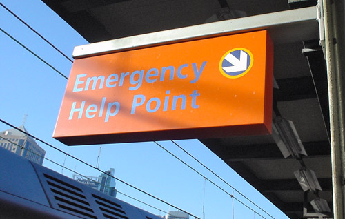 Blue-on-orange sign reads 'Emergency Help Point'