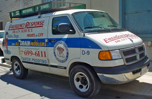 White delivery van reads 'Emergency Response Drain Service... for All Drain Problems' in garish yellow, blue, and red type