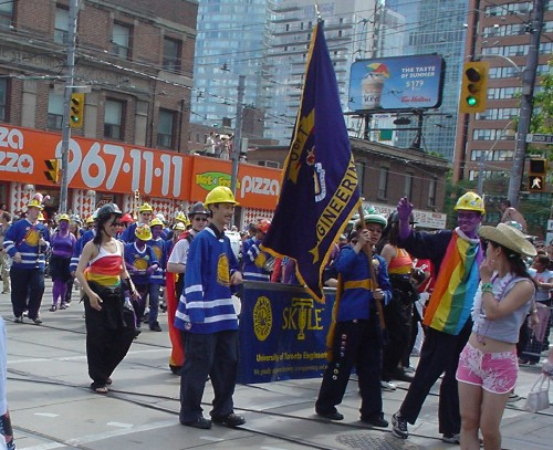 Young men and a few women in hardhats and blue face paint carry a SKULE banner