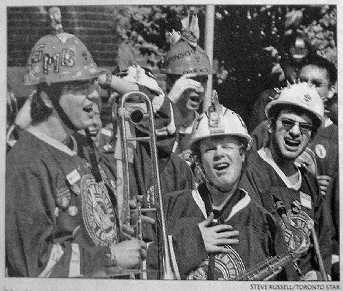 Young guys in hardhats and hockey jerseys, one holding a trombone