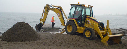 At shore of beach, a backhoe digs into sand as a large pile of sand sits nearby. Man in orange vest and hard hat watches from nearby sandbar