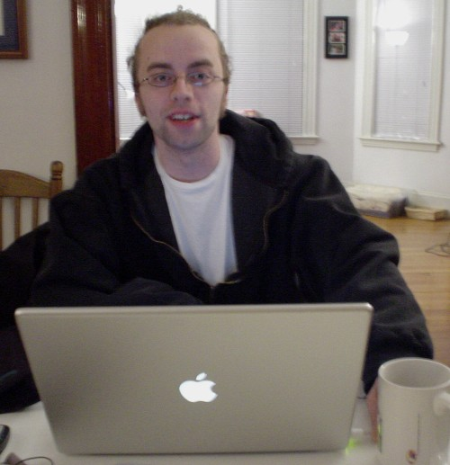 Man smiles at camera as he sits with PowerBook