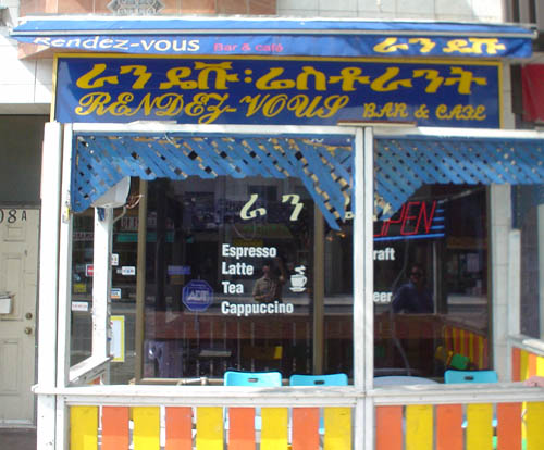 Sign over café is written in yellow type on a blue background, with a line of Amharic and a line of script capitals reading RENDEZ-VOUS BAR & CAFE
