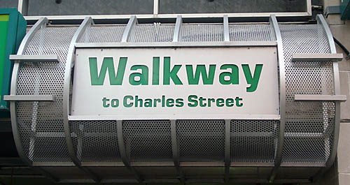 Sign face inset into barrel-shaped currgated-steel frame reads Walkway to Charles Street in Eurostyle