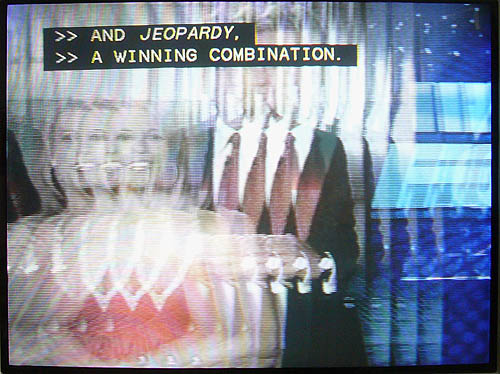 Jittery, fragmented TV image has clear captioning reading AND JEOPARDY. A WINNING COMBINATION