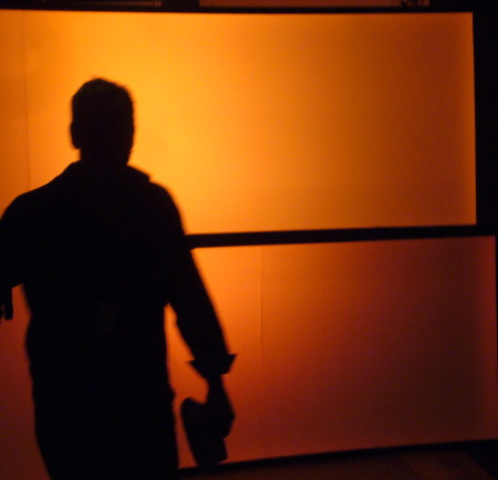 Man silhouetted against glowing orange scrims