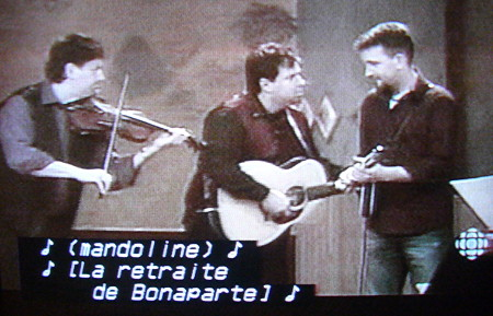 Fiddler, guitarist, and mandolinist play, with captions reading ♪ (mandoline) ♪ 