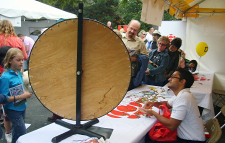 CBC table at outdoor fair has large vertical spinning wheel, its blank plywood back visible