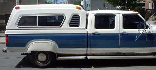 Old blue king-cab pickup truck has elaborate cap and white fender skirts
