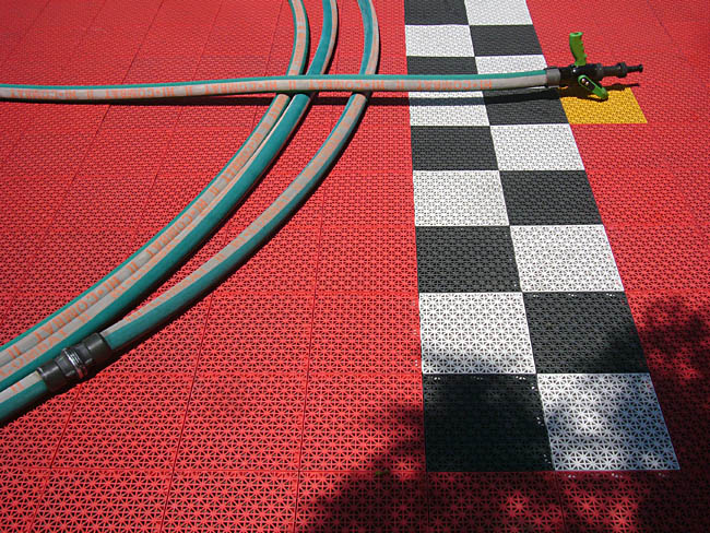 Black-and-white checkerboard pattern on a red textured floor, with orange-and-green hose laid on top