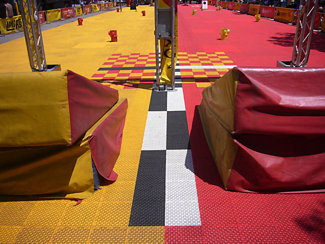 Angled pads in red and yellow and yellow and red sit at the end of individual red and yellow race courses