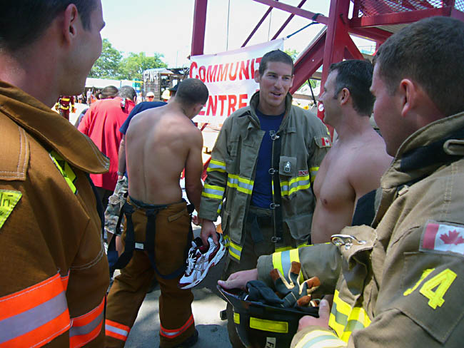 Five firemen, two of them shirtless, standing around talking