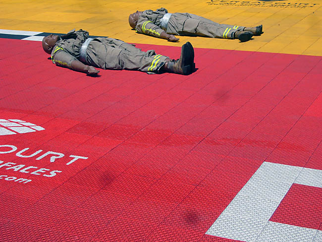 Male mannequins in full turnout gear lay, one each, on red tiles and yellow tiles