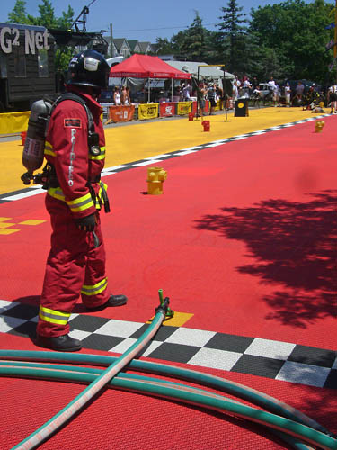 Fireman in red suit and air tank looks down the length of a red race course