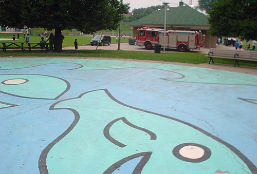 A nearby wading-pool floor, with painted blue-and-green whales, looms across the picture while a red firetruck sits parked alongside a building in the distance