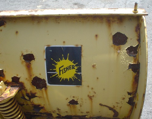Yellow metal plane has rust spots and a large attached spring. Half a blue sign shows the word FISHER on a yellow blot