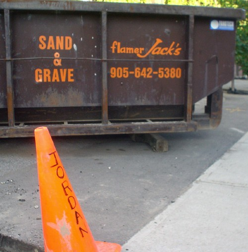 Orange pylon labelled JORDAN sits in front of brown dumpster with the legend flamer Jack's SAND & GRAVE 905-642-5380