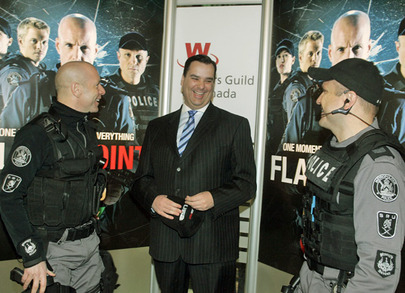 Hugh Dillon and Enrico Colantoni, in SWAT-like uniforms, flank James Moore, in a suit