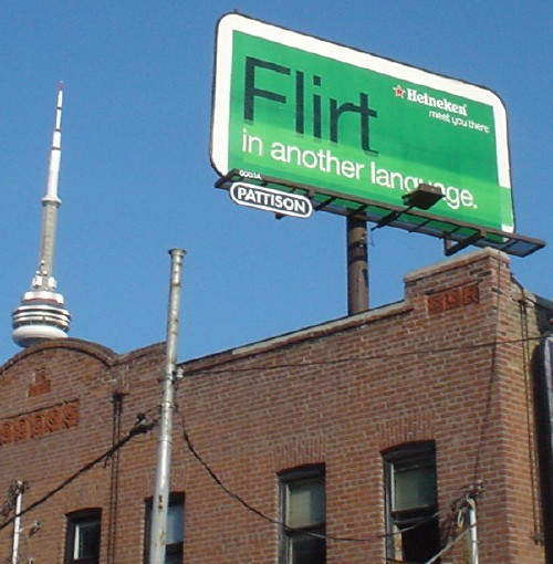 Green billboard for Heineken reads 'Flirt in another language,' with the rt letters touching