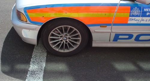 White car has fluorescent orange and yellow stripes on the front quarter panel, with METROPOLITAN POLICE labels partly visible