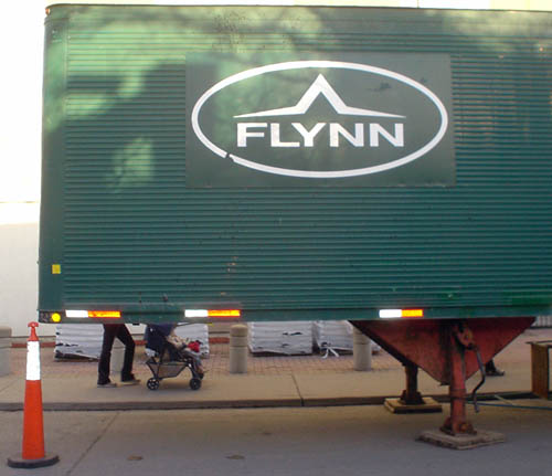 Legs push baby carriage behind a green transport trailer labelled FLYNN