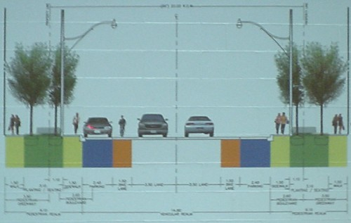 Illustration shows two lanes of traffic in either direction, a sidewalk, a light standard and pair of trees, and another sidewalk