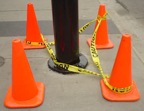 Four bright-orange pylons draped with yellow CAUTION tape surround a shiny black pole