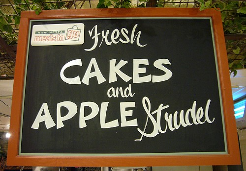 Handlettered chalkboard sign reads Fresh Cakes and Apple Strudel in upright and cursive