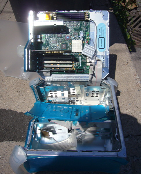 Blue PowerMac G3 sits open and picked clean on the sidewalk, metal corner glinting in the sun